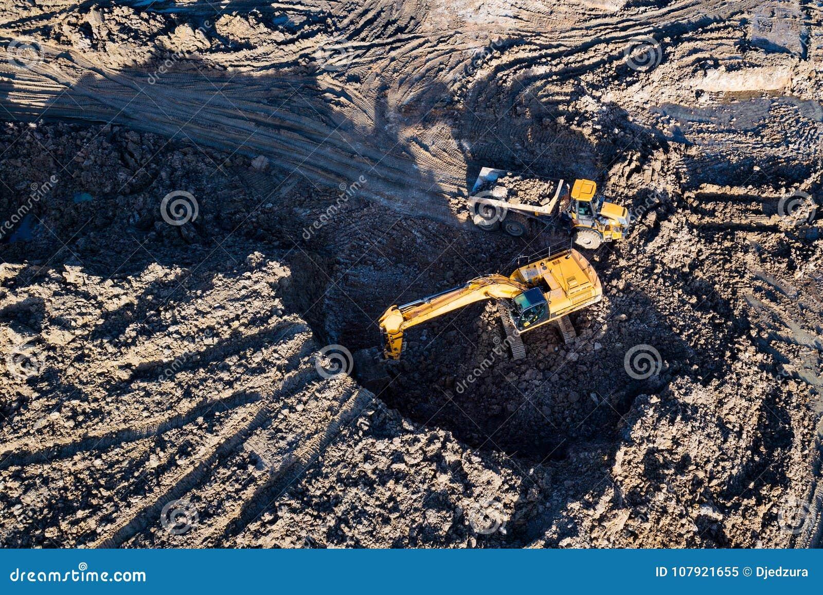 Flyg- surrsikt av grävskopan som laddar person som ger drickslastbilen