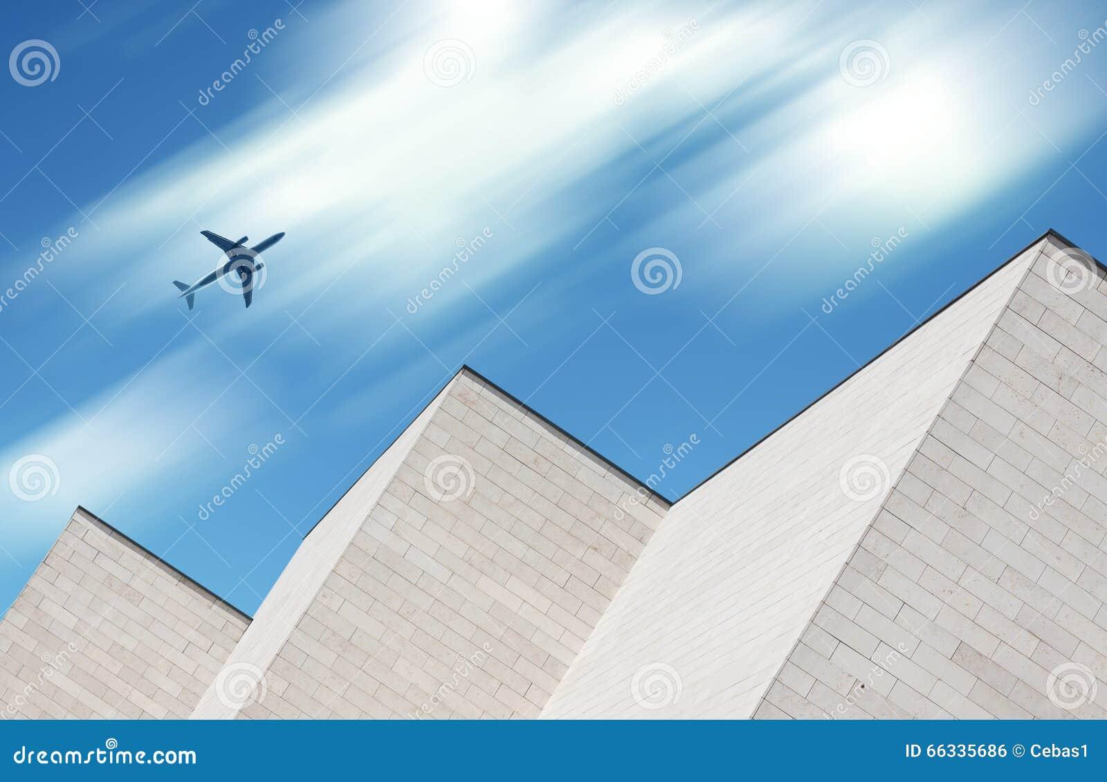 Flygplan som flyger över modern byggnad