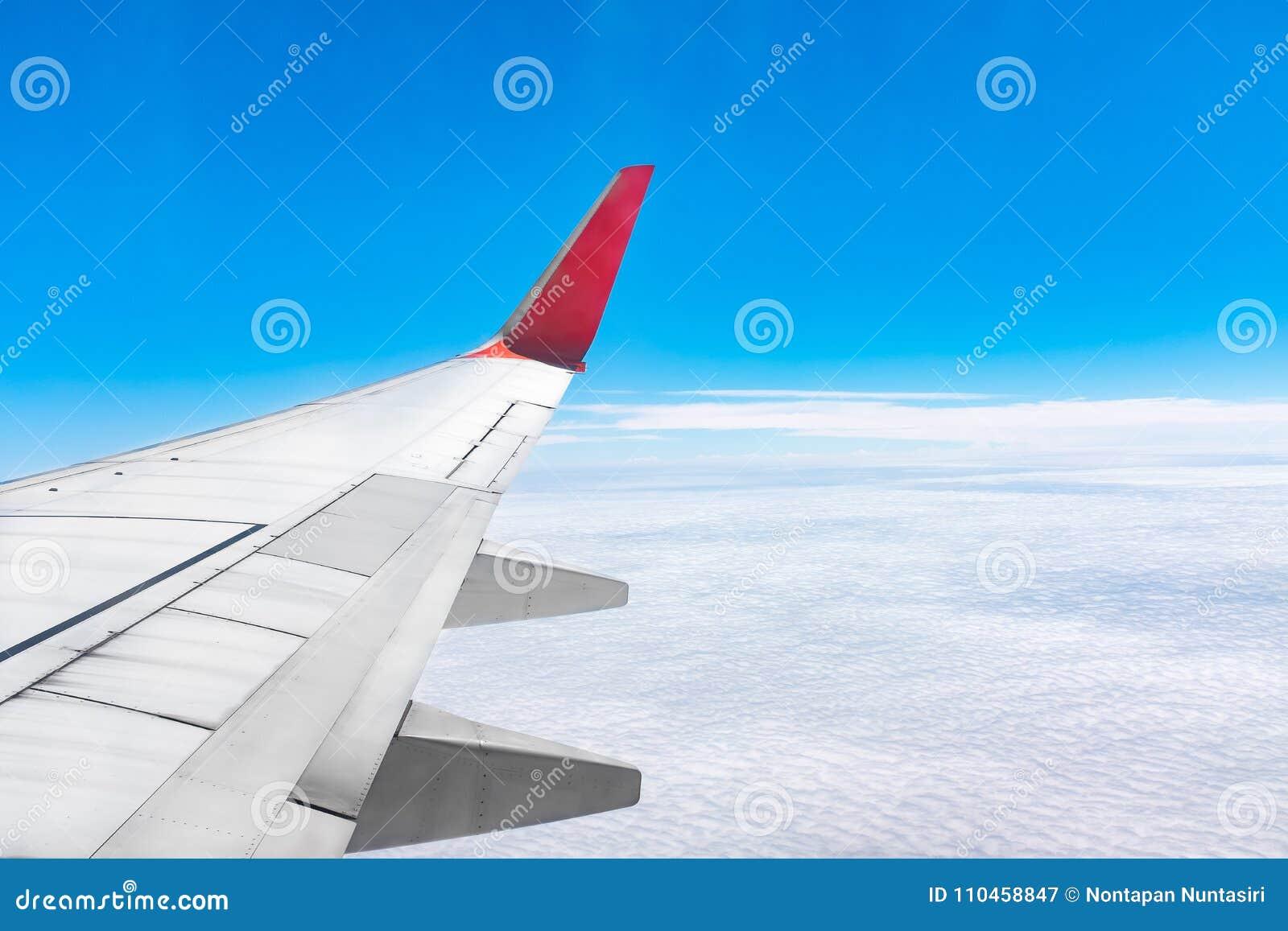 Flygplanvinge som flyger ovannämnda moln