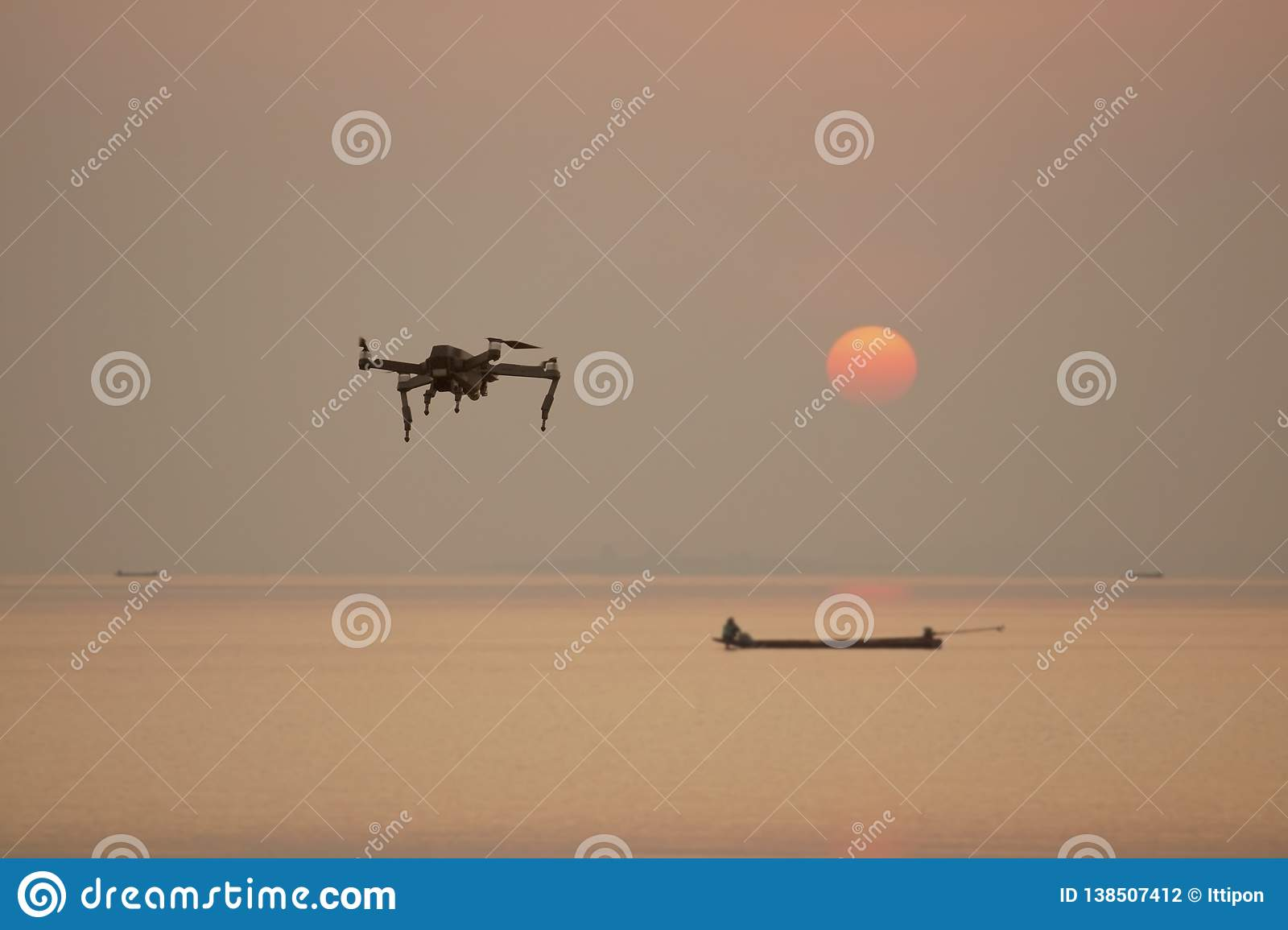 Flying drone on the sea with sunset