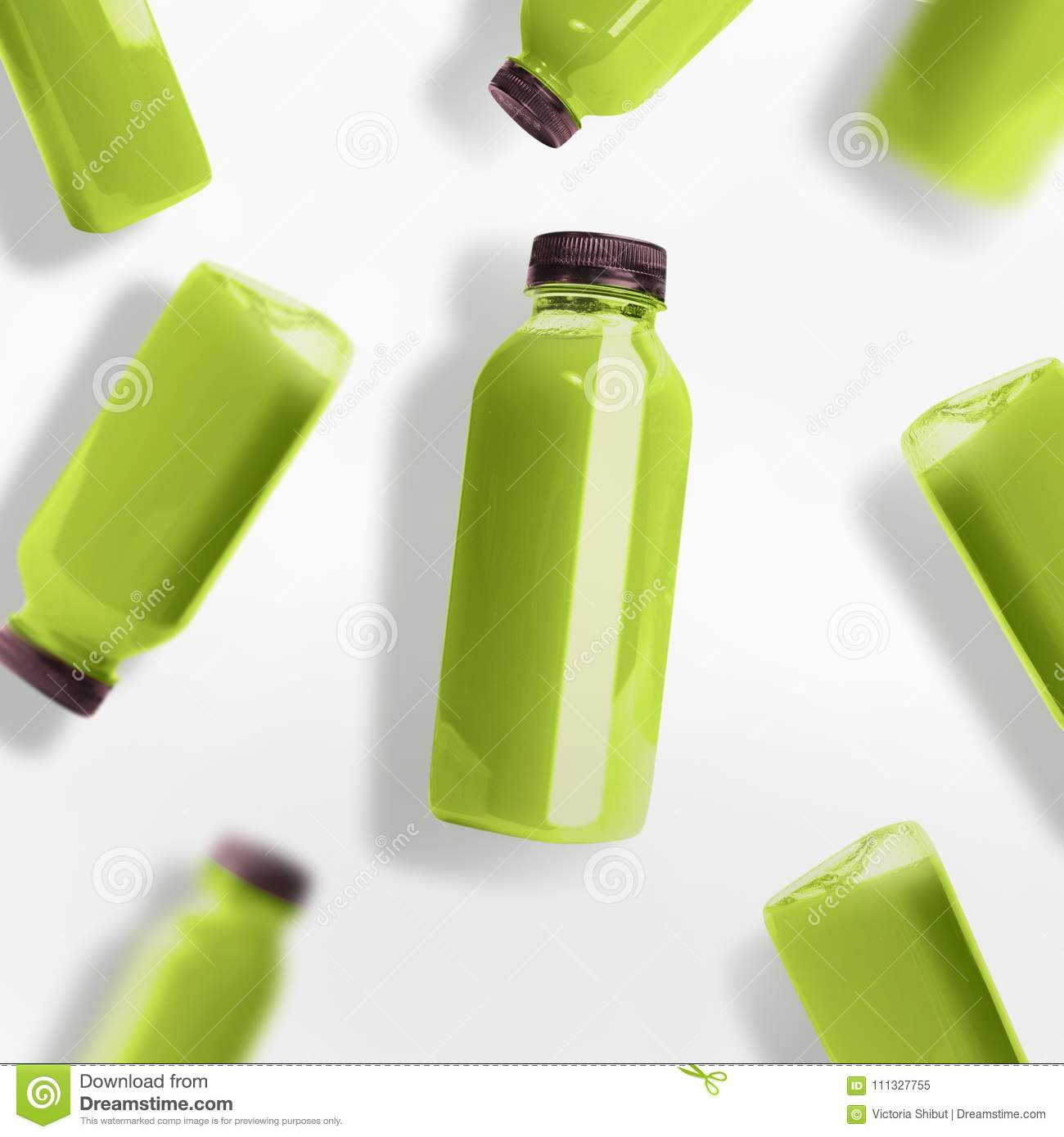 Flying green smoothie or juice bottles pattern on white background, top view