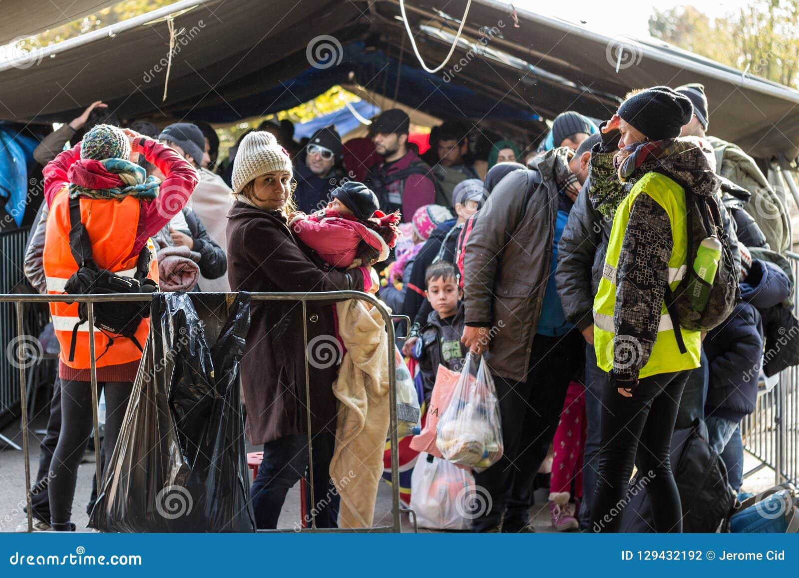 Flyktingkvinna som rymmer hennes barn, en behandla som ett barn som står i mitt av en folkmassa på den KroatienSerbien gränsen, p