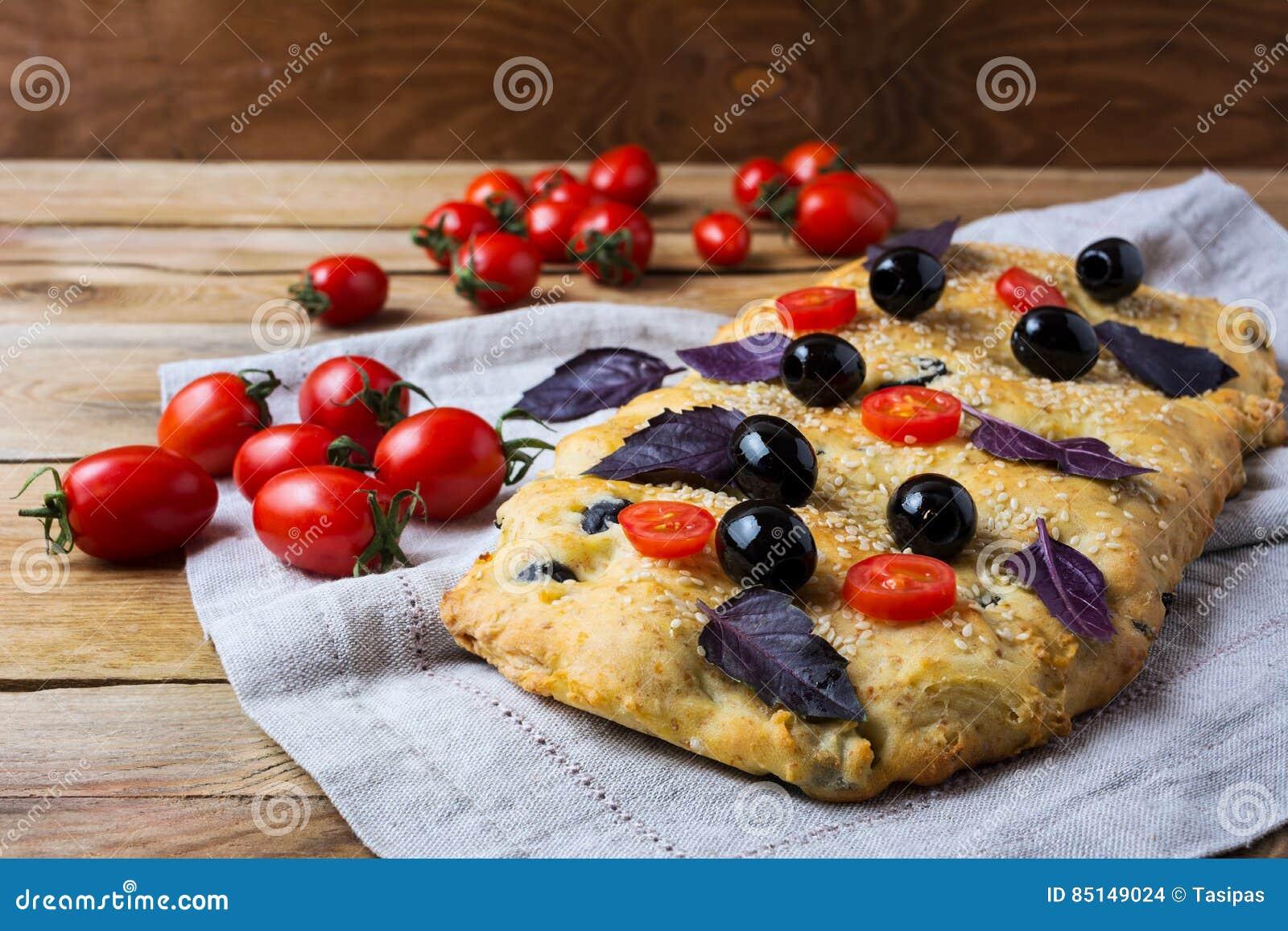 Focaccia com azeitona, tomate de cereja e folhas da manjericão