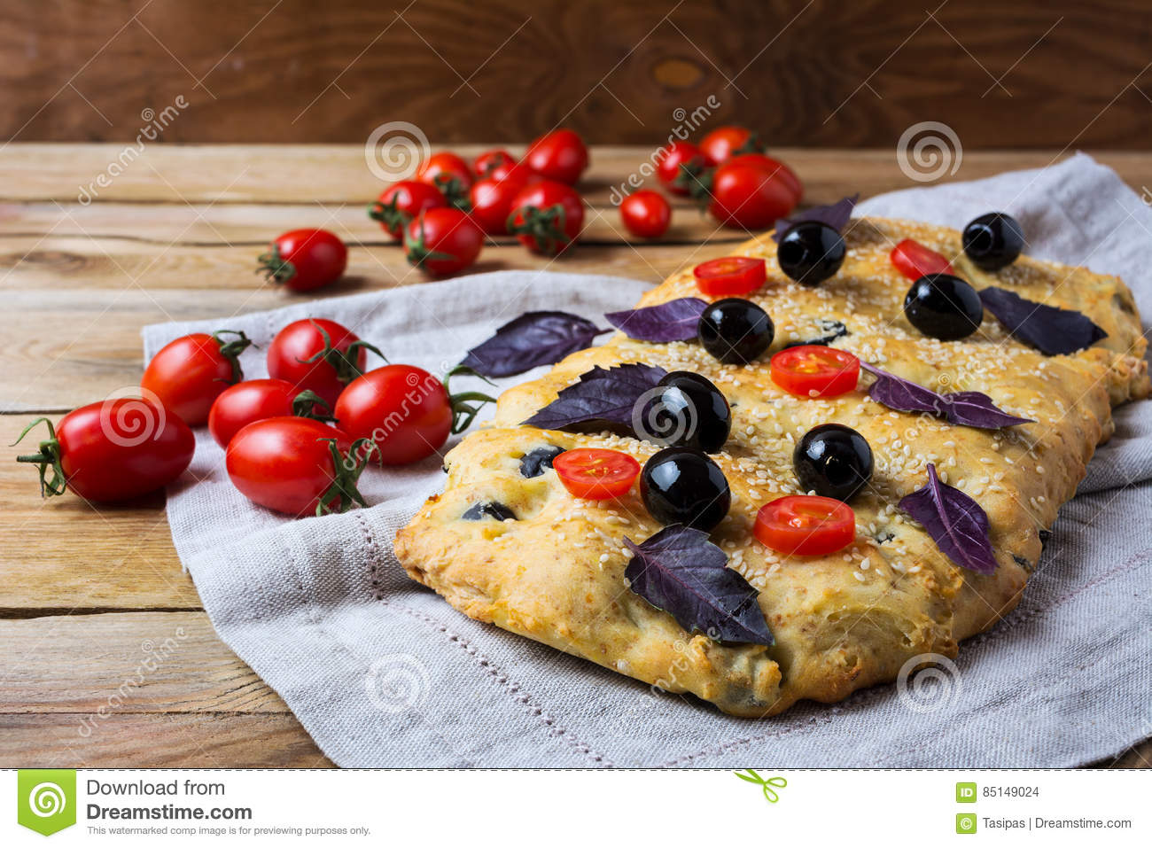 Focaccia with olive, cherry tomato and basil leaves