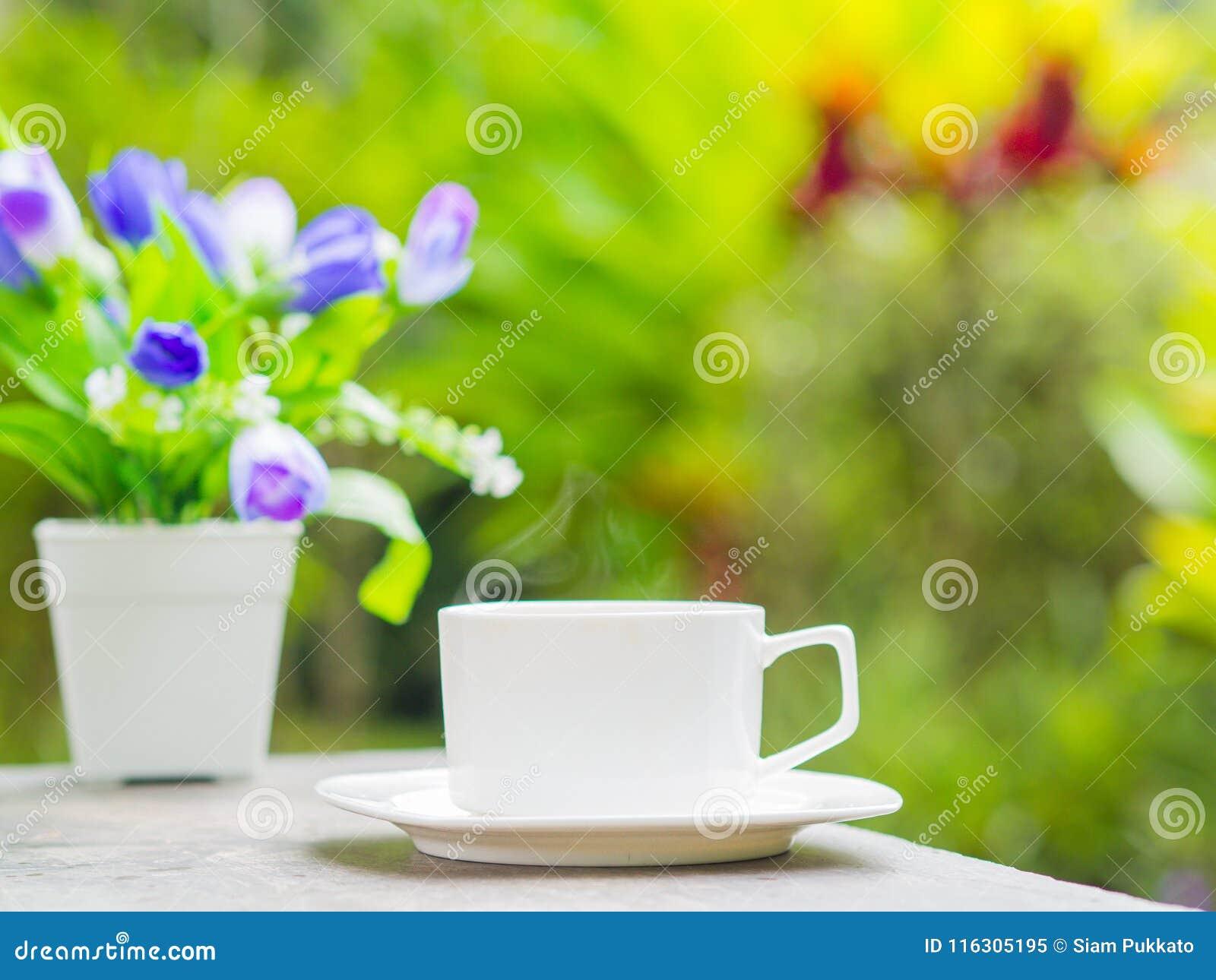 Foco macio do fim acima do copo de café no jardim