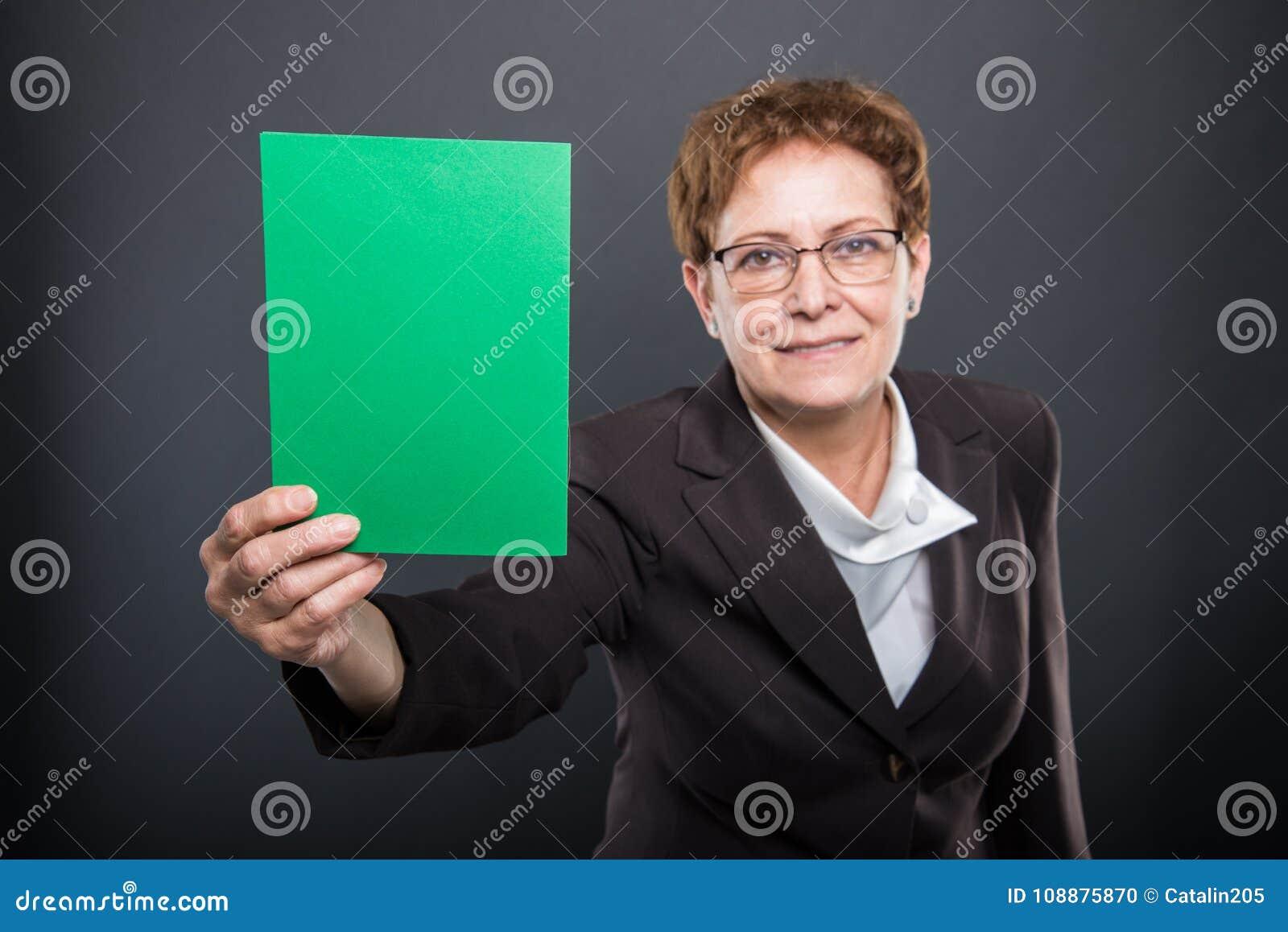 Foco selectivo de la señora mayor del negocio que sostiene la cartulina verde