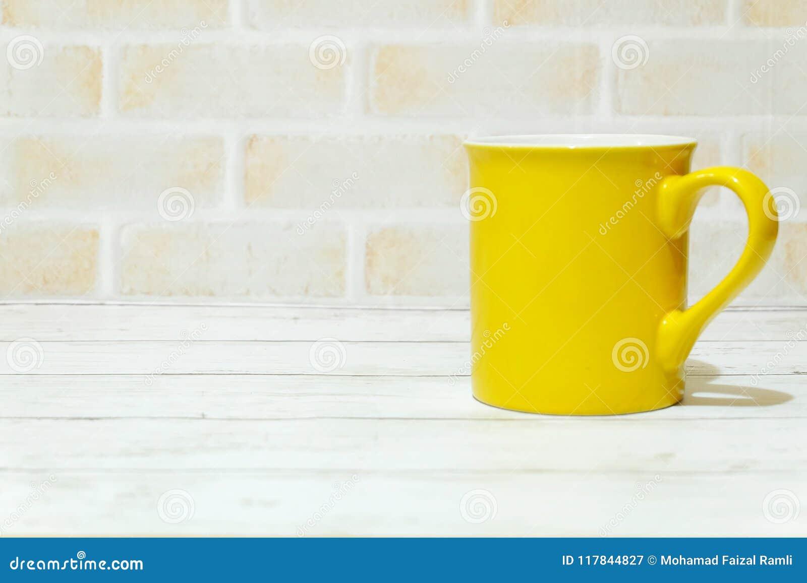 Foco selectivo de la taza amarilla aislado con el espacio de la copia para el texto