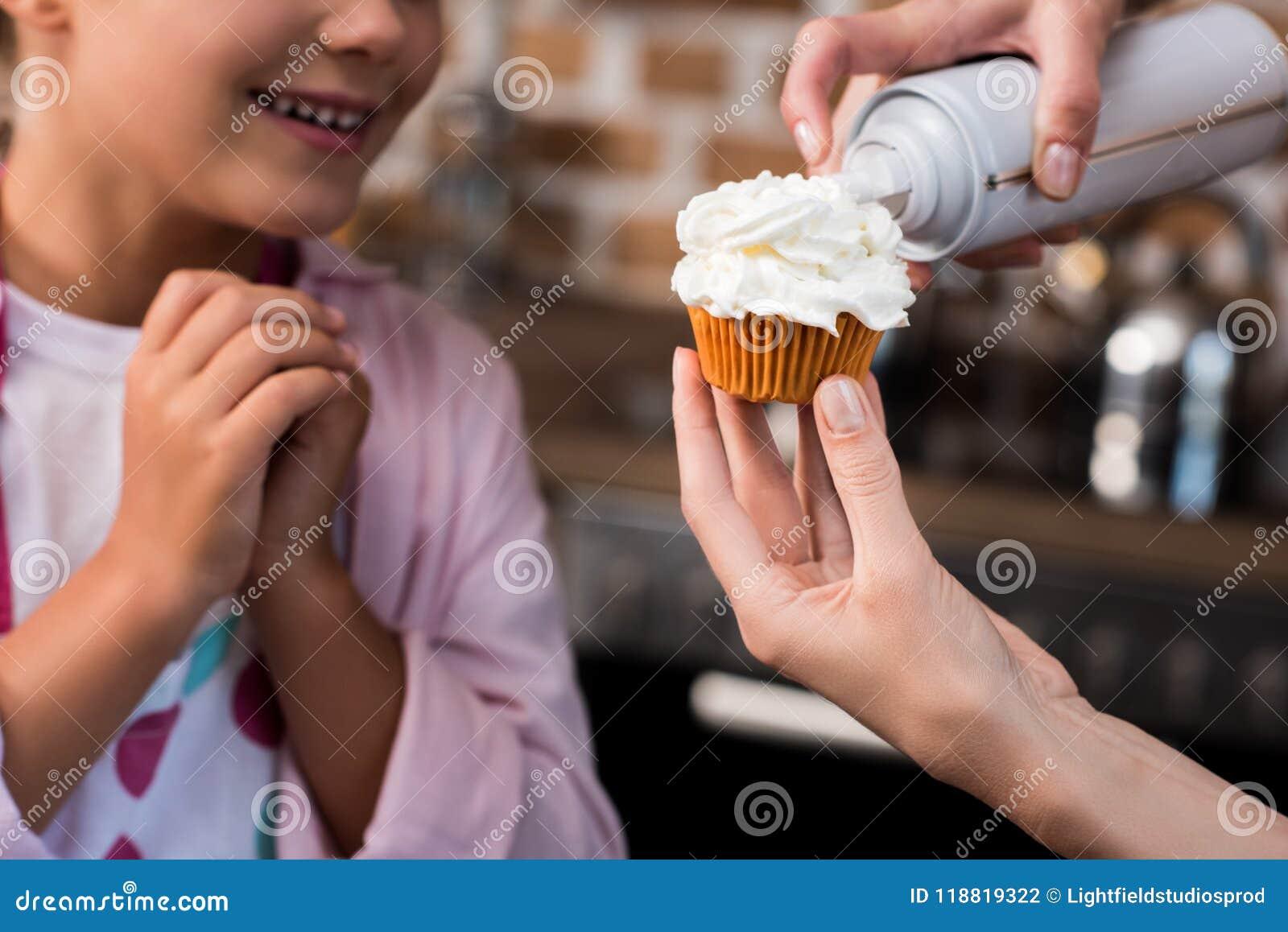 Foco seletivo da mulher que põe o buttercream sobre o queque quando posição da filha