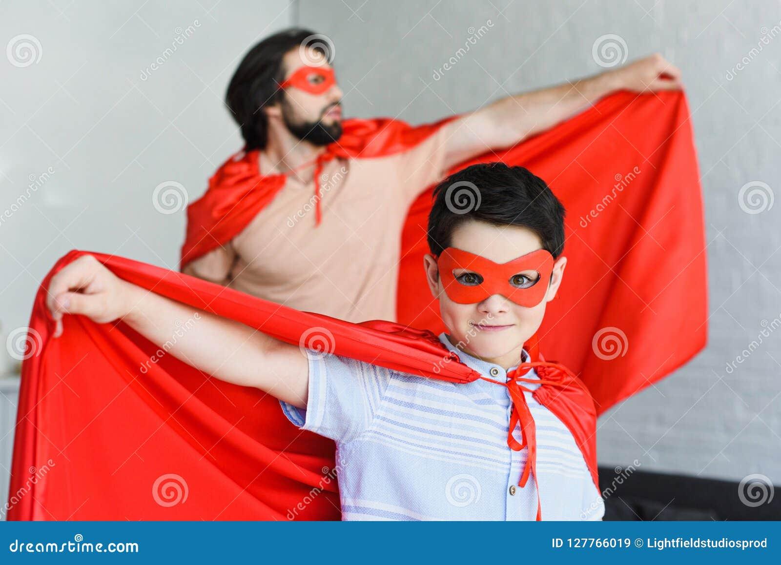 Foco seletivo de poucos filho e pai em trajes vermelhos do super-herói
