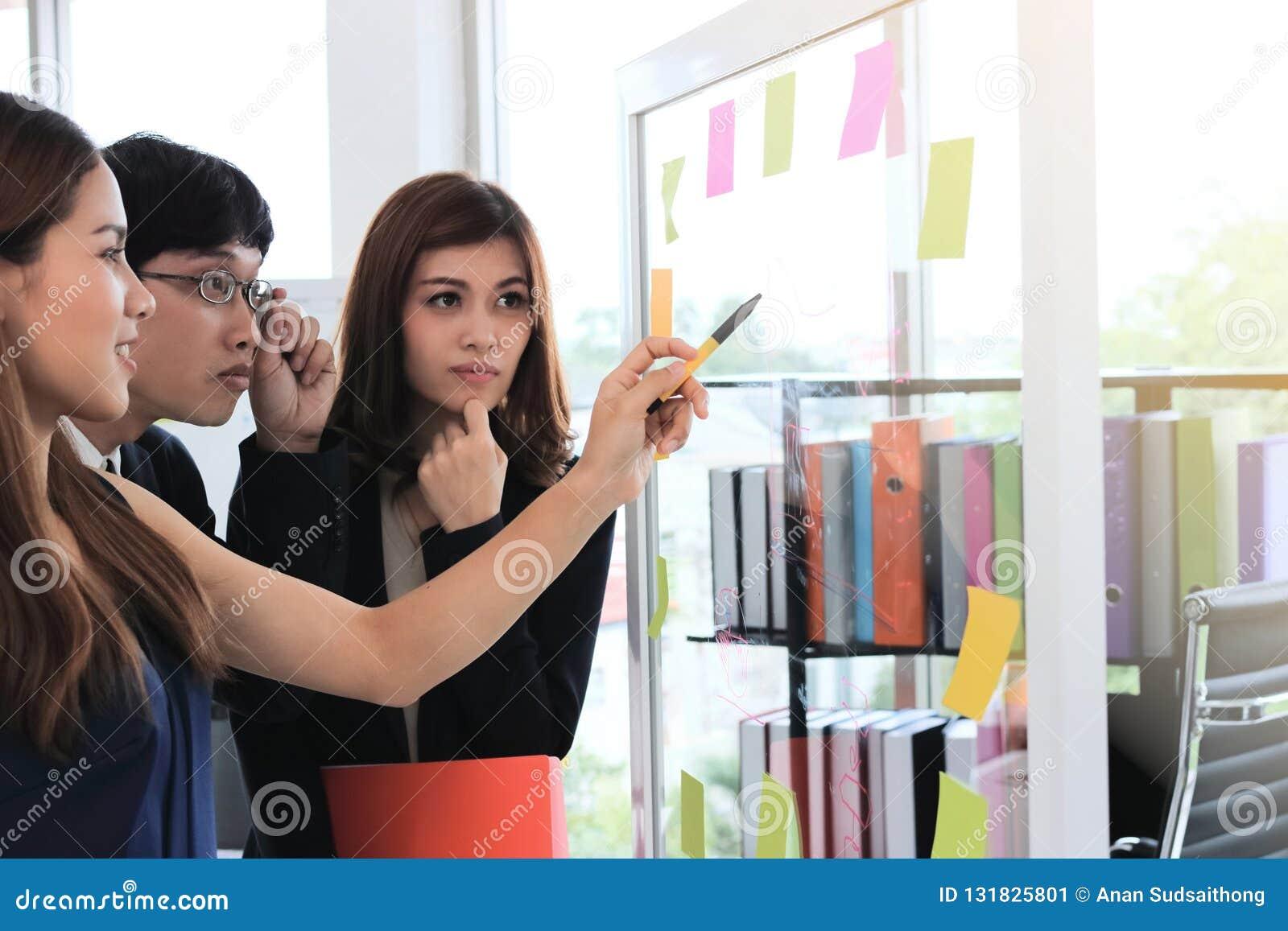 Foco seletivo nas mãos dos executivos asiáticos novos que explicam estratégias na aleta na sala de conferências
