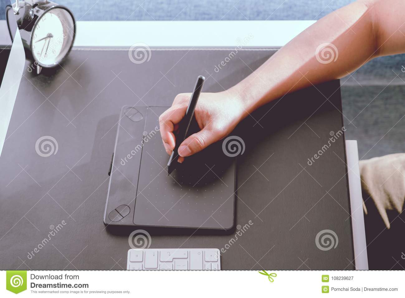 Focus on the busy graphic designer working on computer by digital pen mouse, noise filter apply