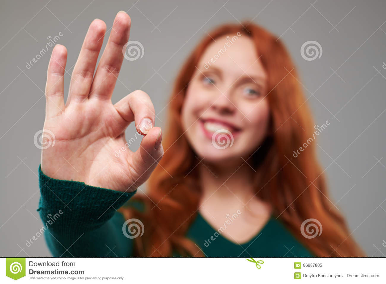 Focus on a gesture of success given by redhead woman
