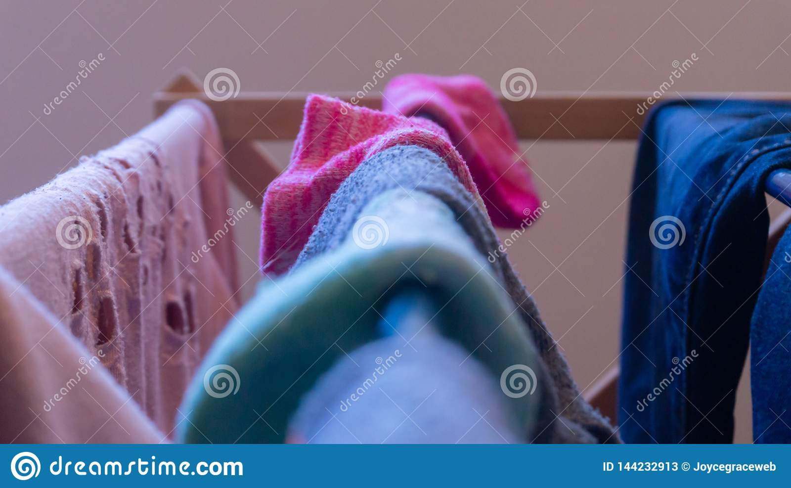 Focus on a pink sock drying on a laundry rack with other woman`s clothes, and mismatched socks blurred in the foreground.