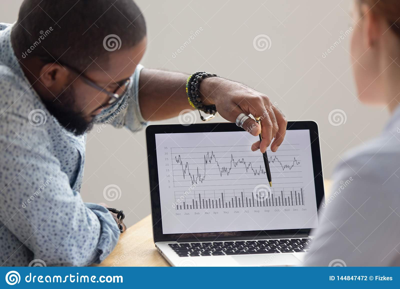 Focused african analyst showing annual financial report on laptop screen