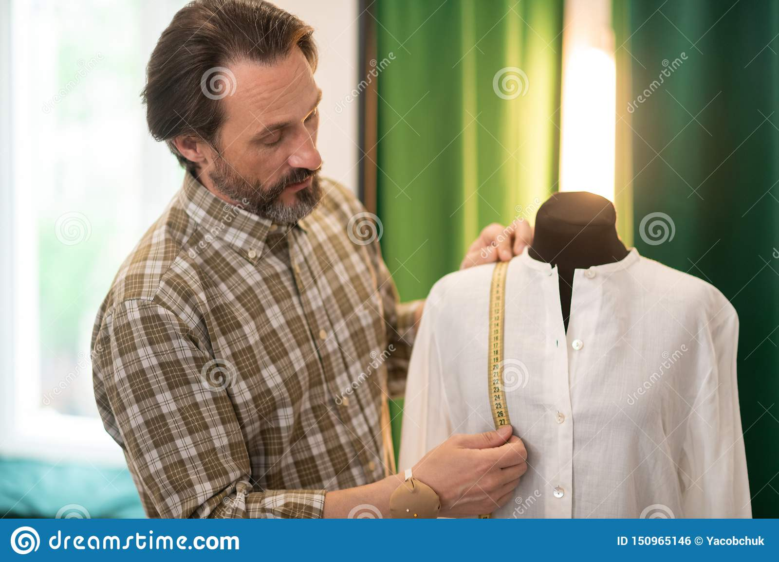 Focused bearded designer getting measurements of a finished white shirt