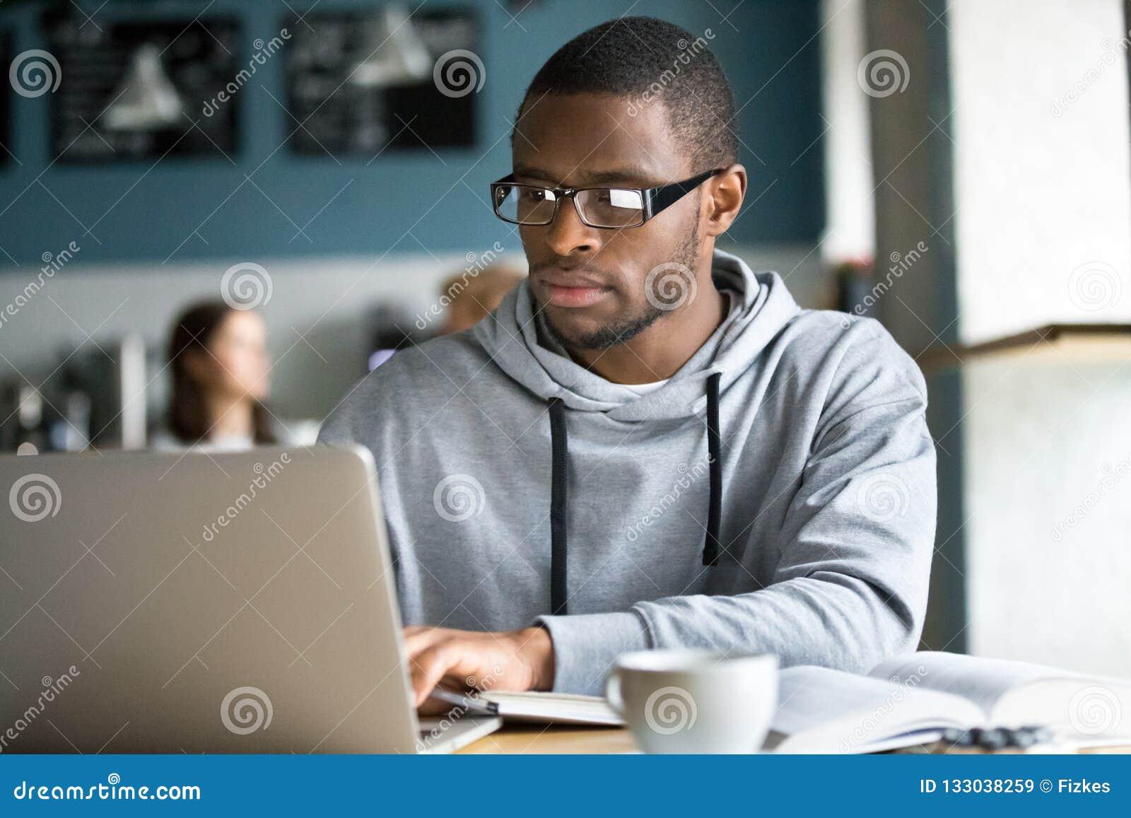 Focused black student studying online in coffeeshop