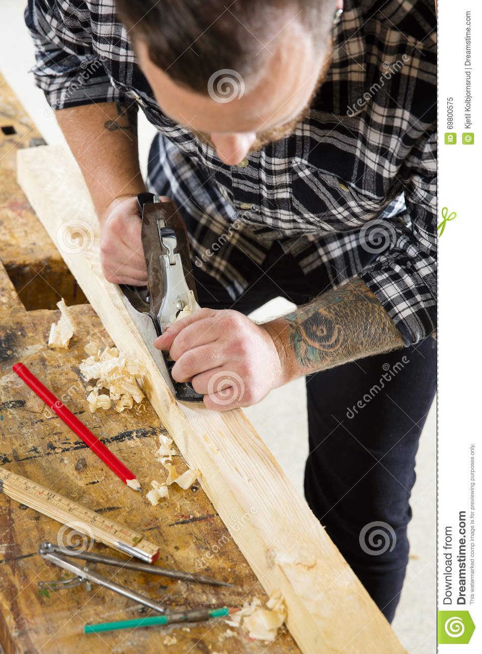Focused carpenter work with plane on wood plank in for Working man tattoo