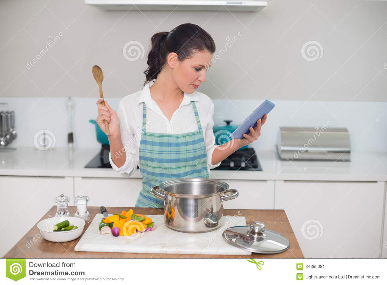 Focused Gorgeous Woman Wearing Apron Using Tablet While