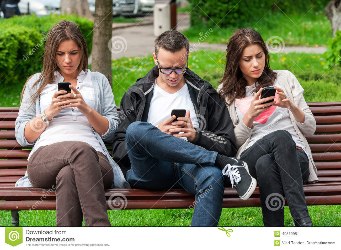 Stock Photo: Focused group of friends looking on their phones and not ...