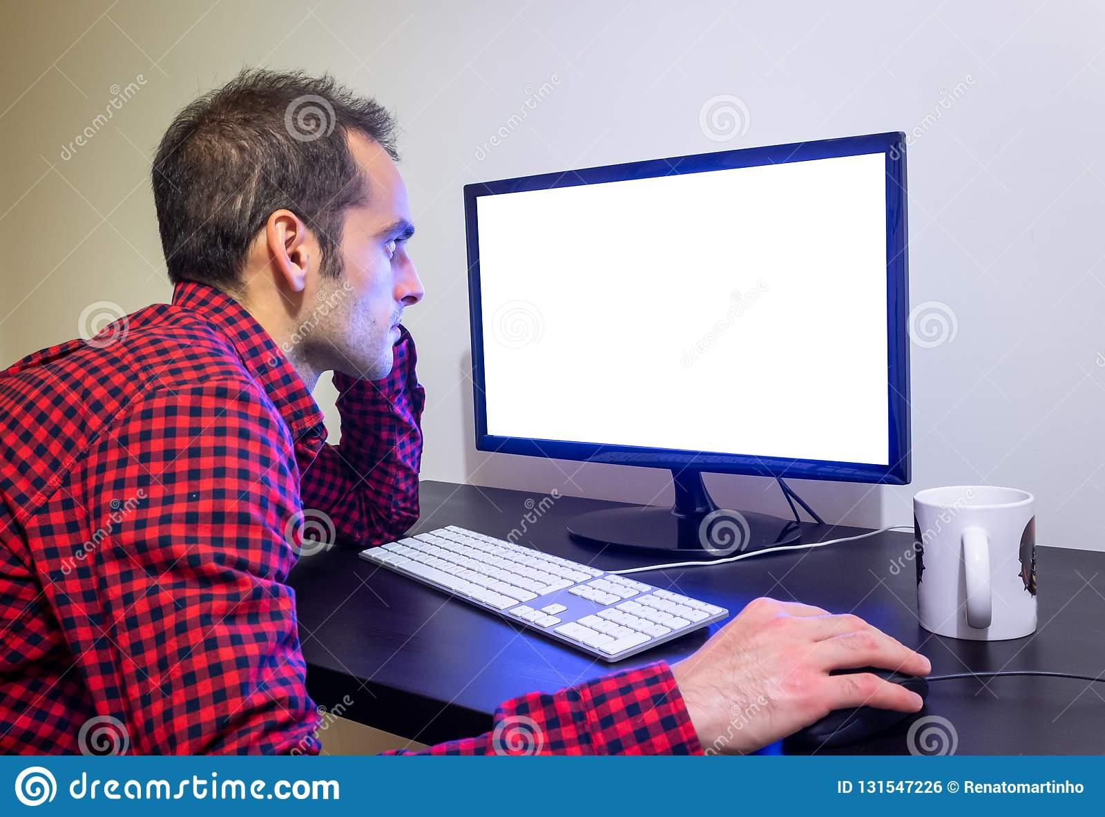 Focused Man Stares at Office Computer on Wooden Black Desk Mockup. Dotted Red Shirt, LCD Screen, Keyboard, Mouse, White Mug. Copy