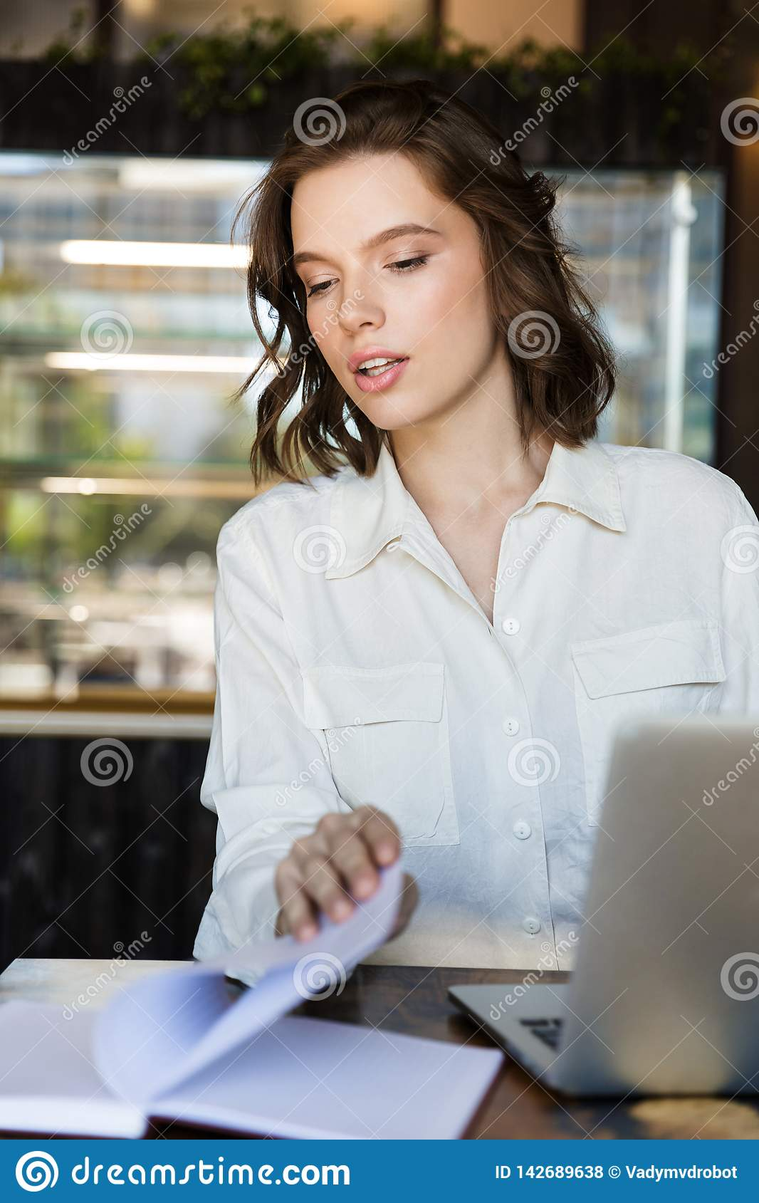 Focused young businesswoman sitting at the cafe indoors