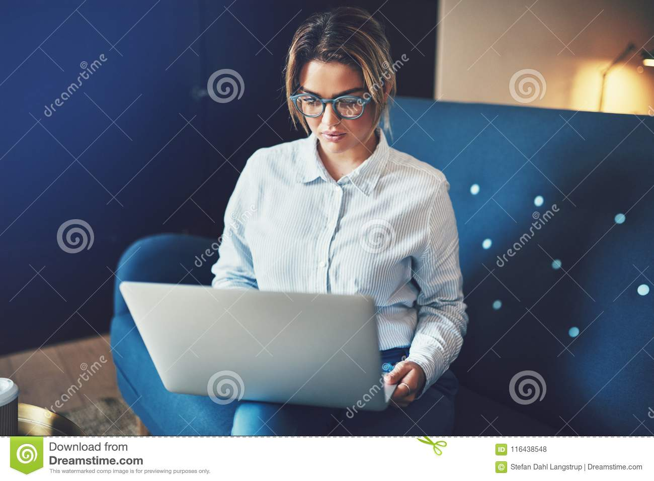 Focused young businesswoman sitting on a sofa working online