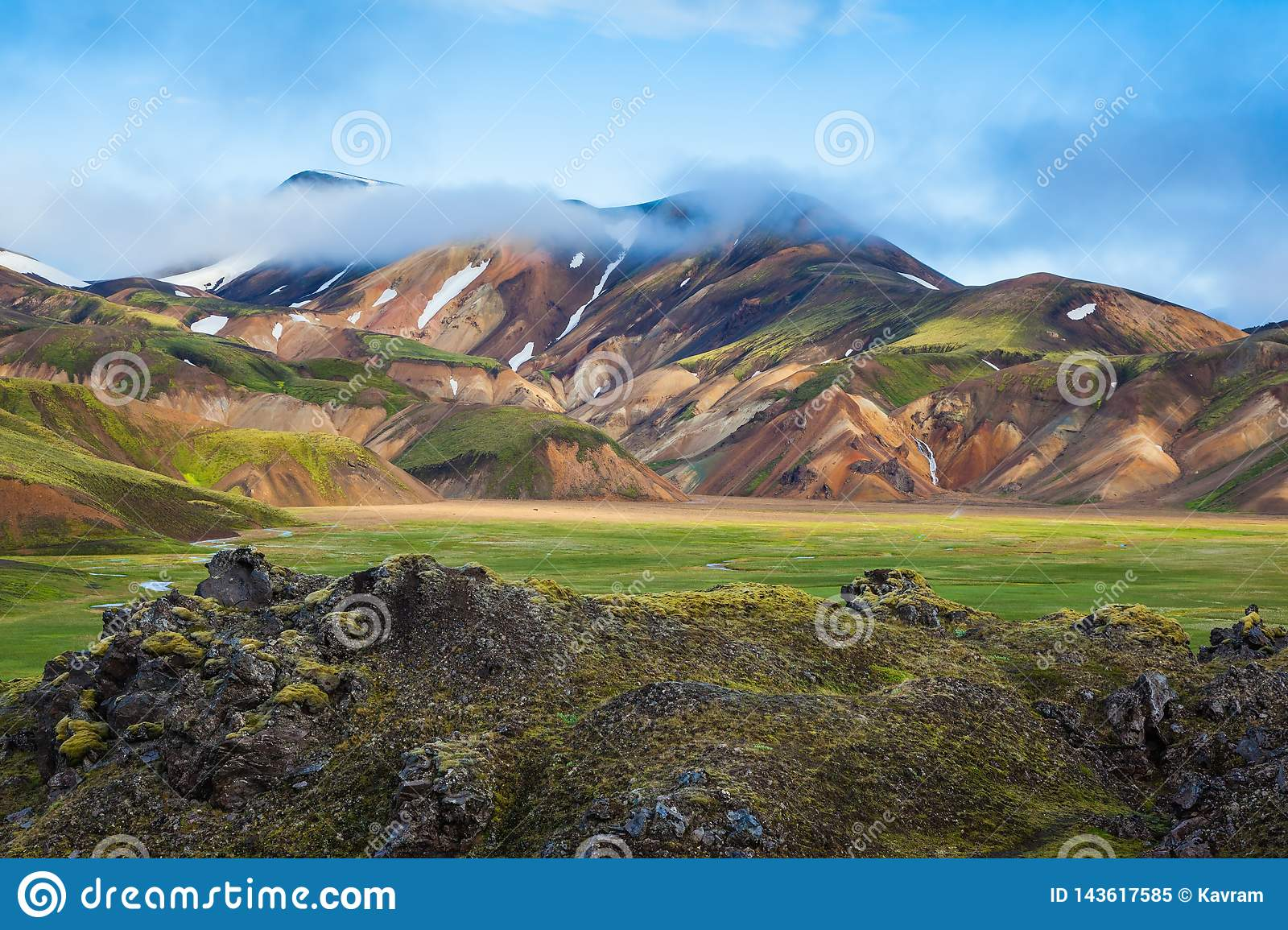 Fog lies in the hollows of colorful mountains