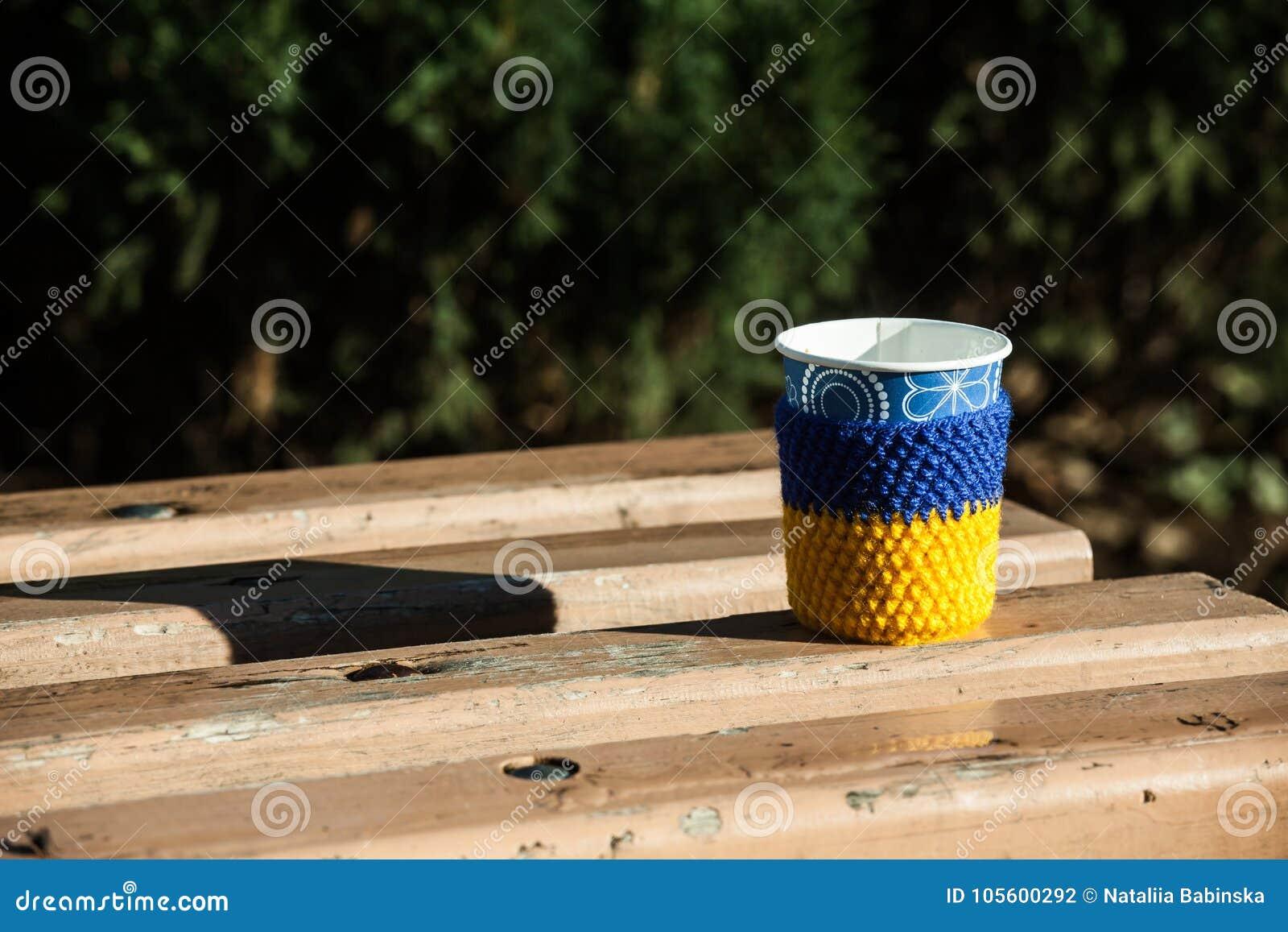 Foggi a coppa tricottare blu coperto del calore di giallo del mornimg della neve del banco di legno del caffè