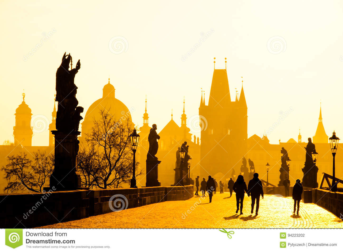 Foggy morning on Charles Bridge, Prague, Czech Republic. Sunrise with silhouettes of walking people, statues and Old