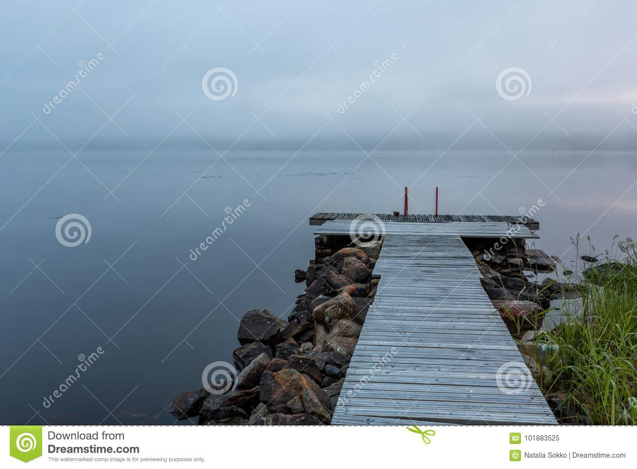 Foggy morning on the lake with pier on foreground