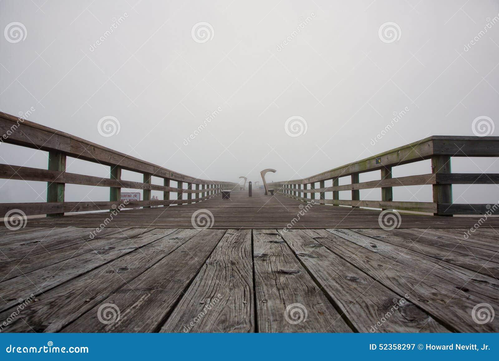 Foggy morning sunrise at pier.