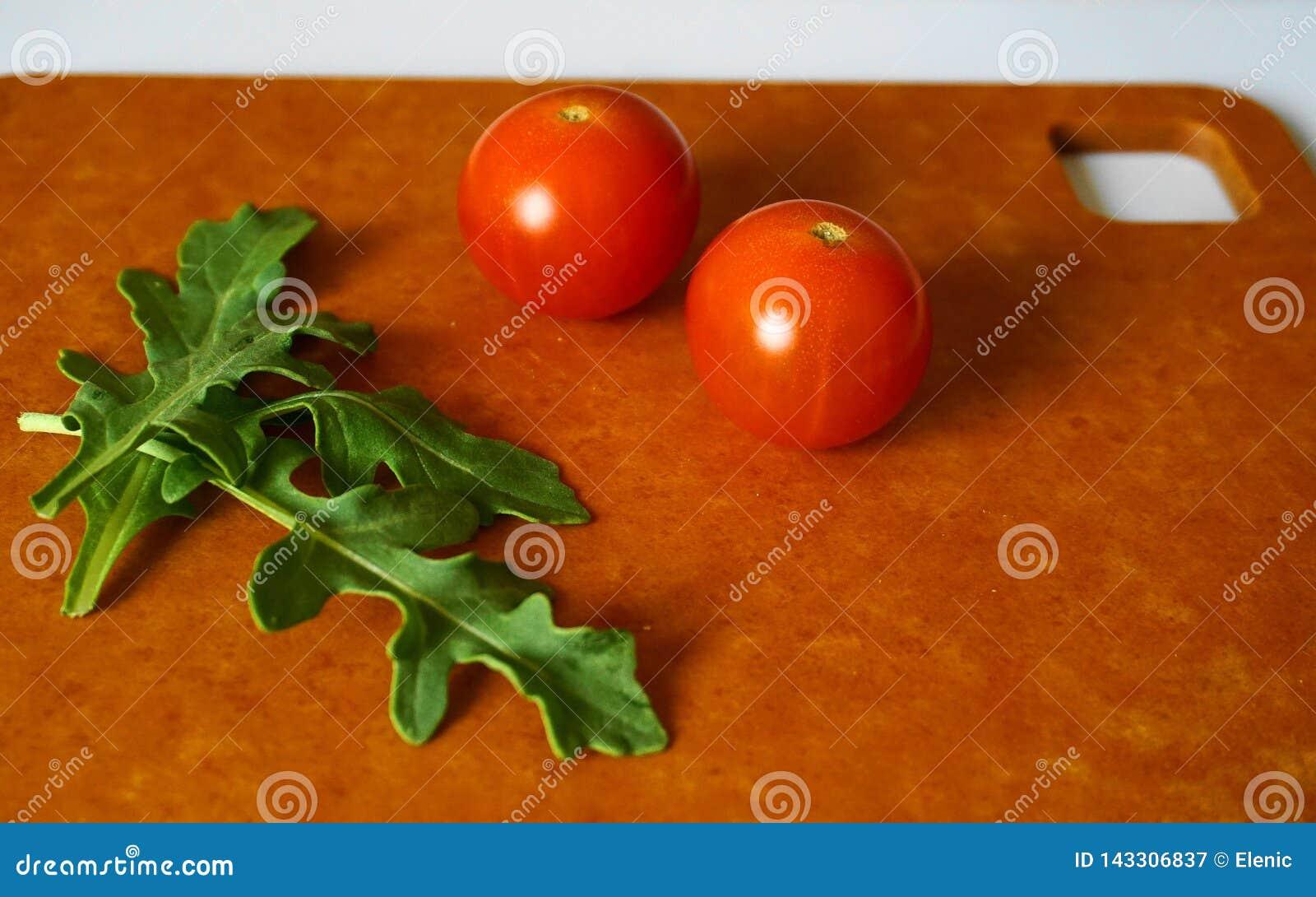 Foglie e pomodori ciliegia verdi freschi della rucola su pannello rigido