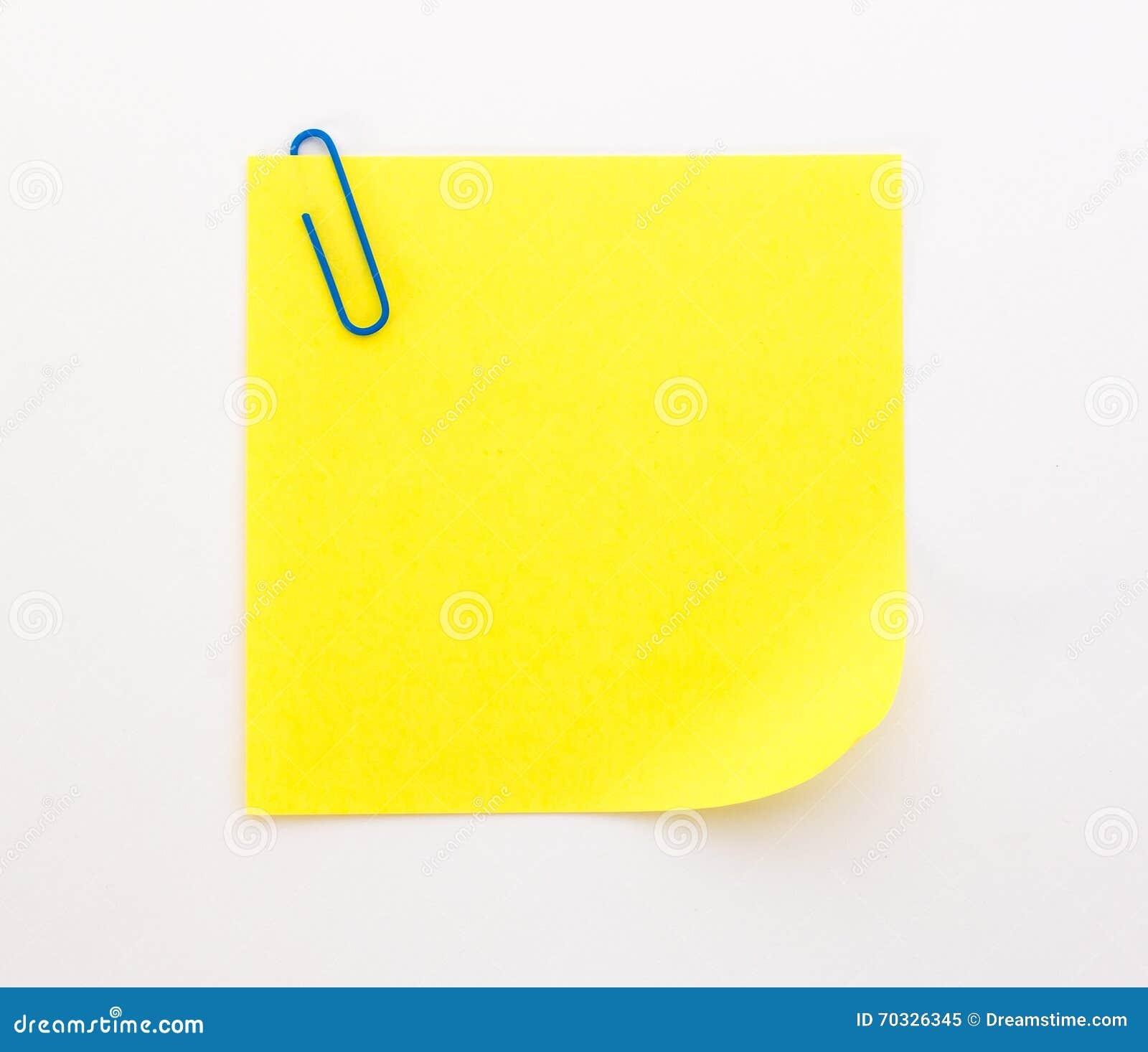 Foglio di carta giallo con la graffetta blu su un fondo - Foglio laminato bianco ...