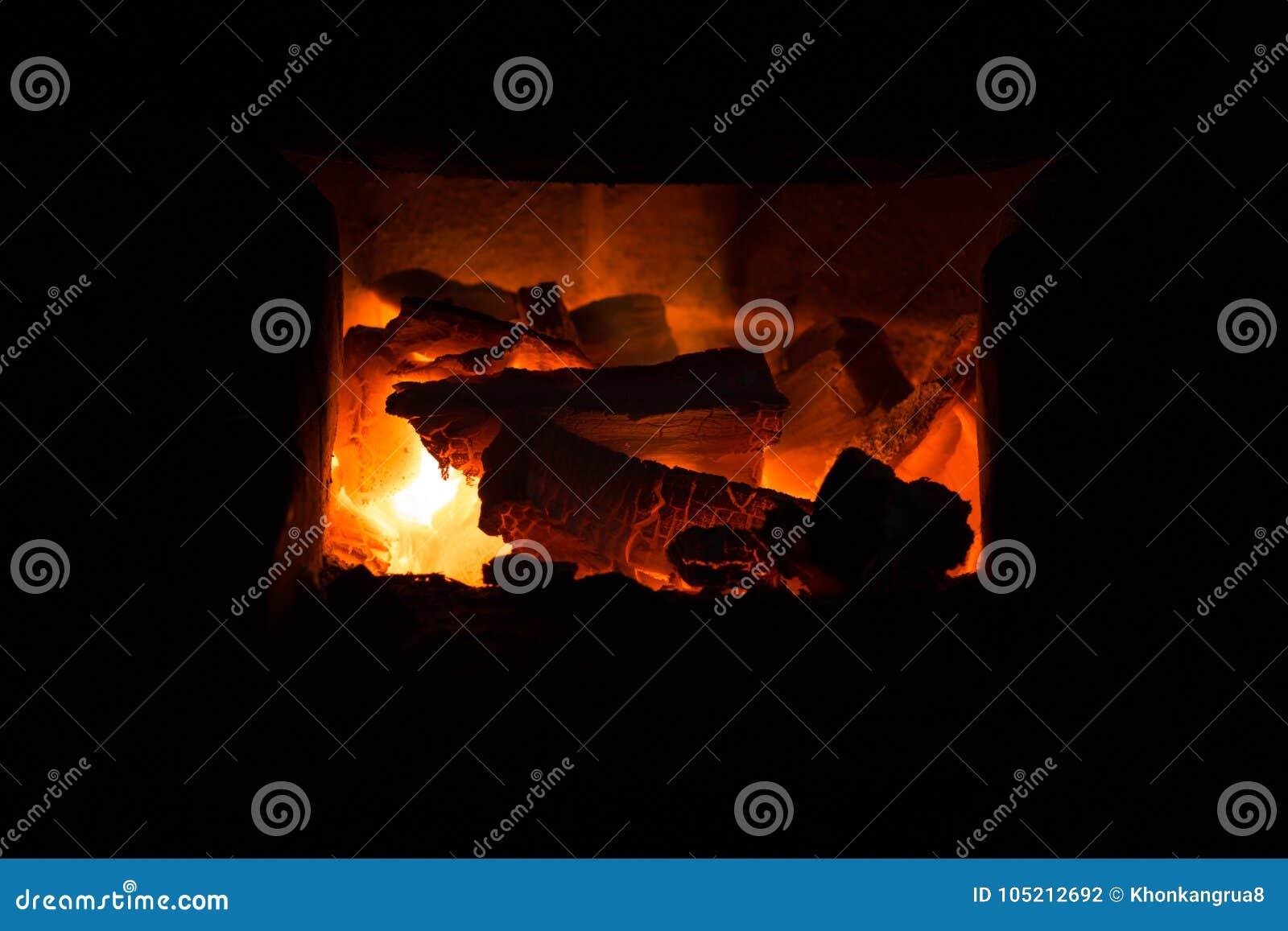 Fogo e carvões na fornalha da chaminé do tijolo