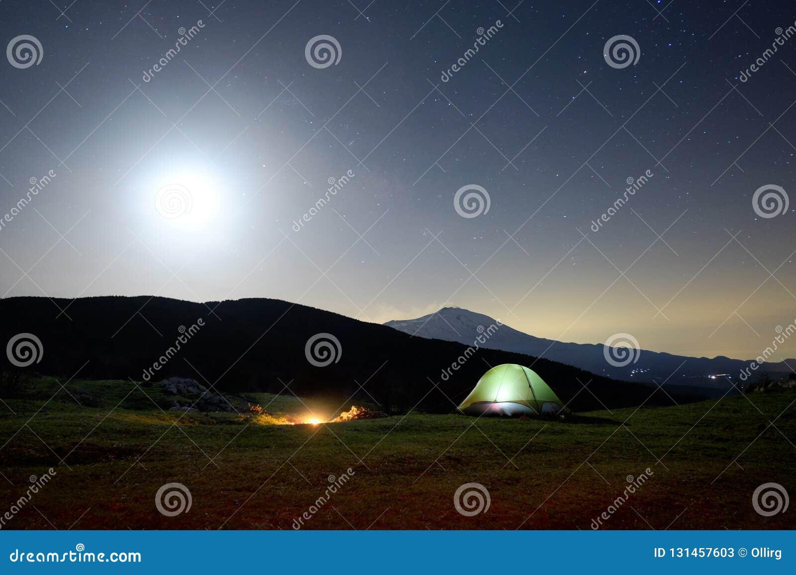 Fogo na noite, na barraca da iluminação e na Etna Volcano sob a luz de lua