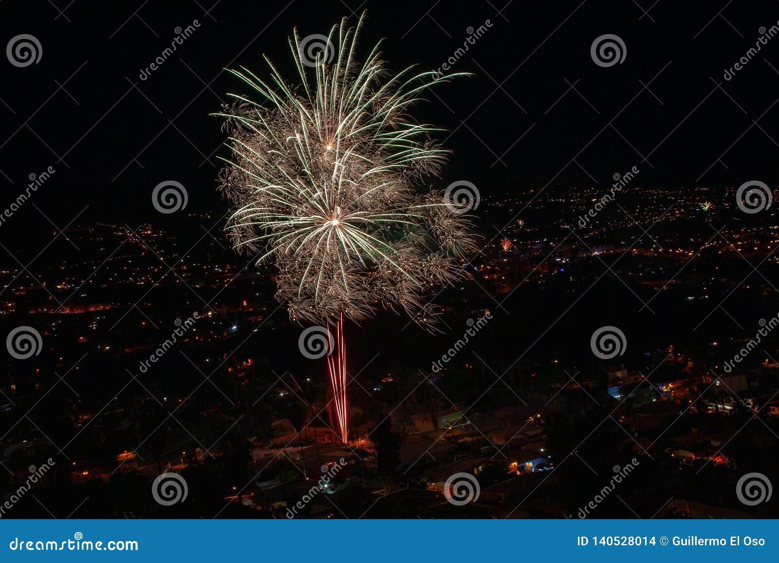 Fogos de artifício grandes sobre uma cidade na noite