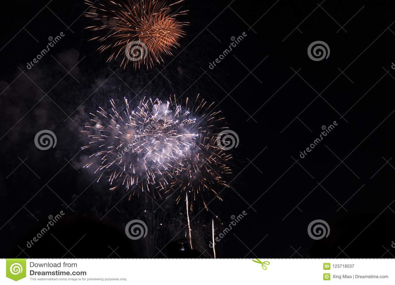 Fogos-de-artifício múltiplos no céu noturno em uma composição nas máscaras vermelhas e brancas