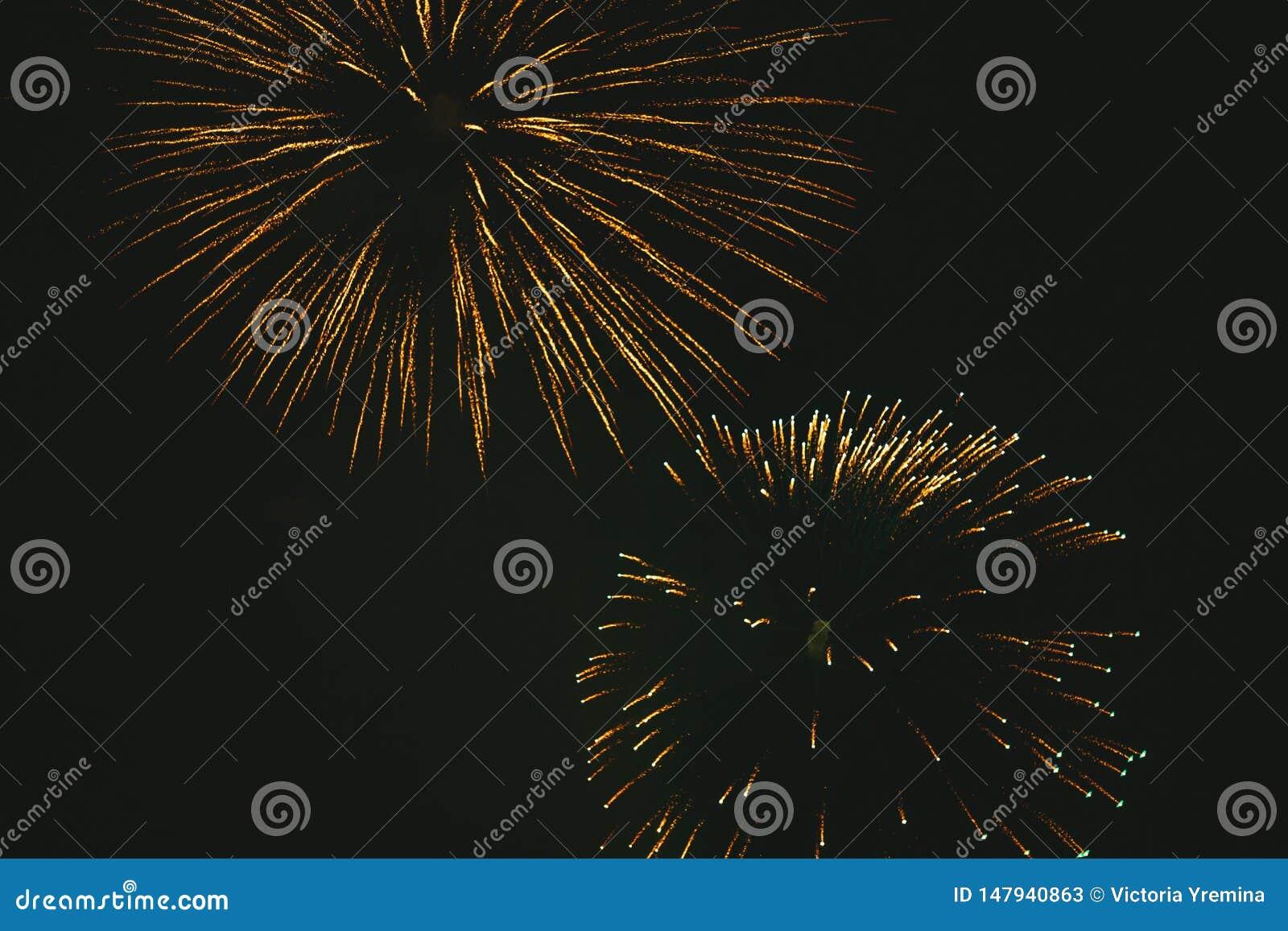 Fogos de artif?cio festivos do ouro do close-up em um fundo preto Fundo abstrato do feriado