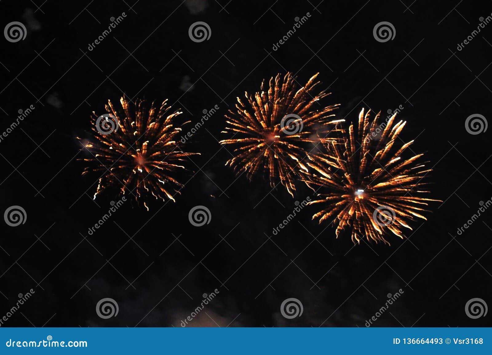 Fogos-de-artif?cio firework Fundo celestial Um trio surpreendente de luzes de cintilação amarelas brilhantes no céu noturno duran