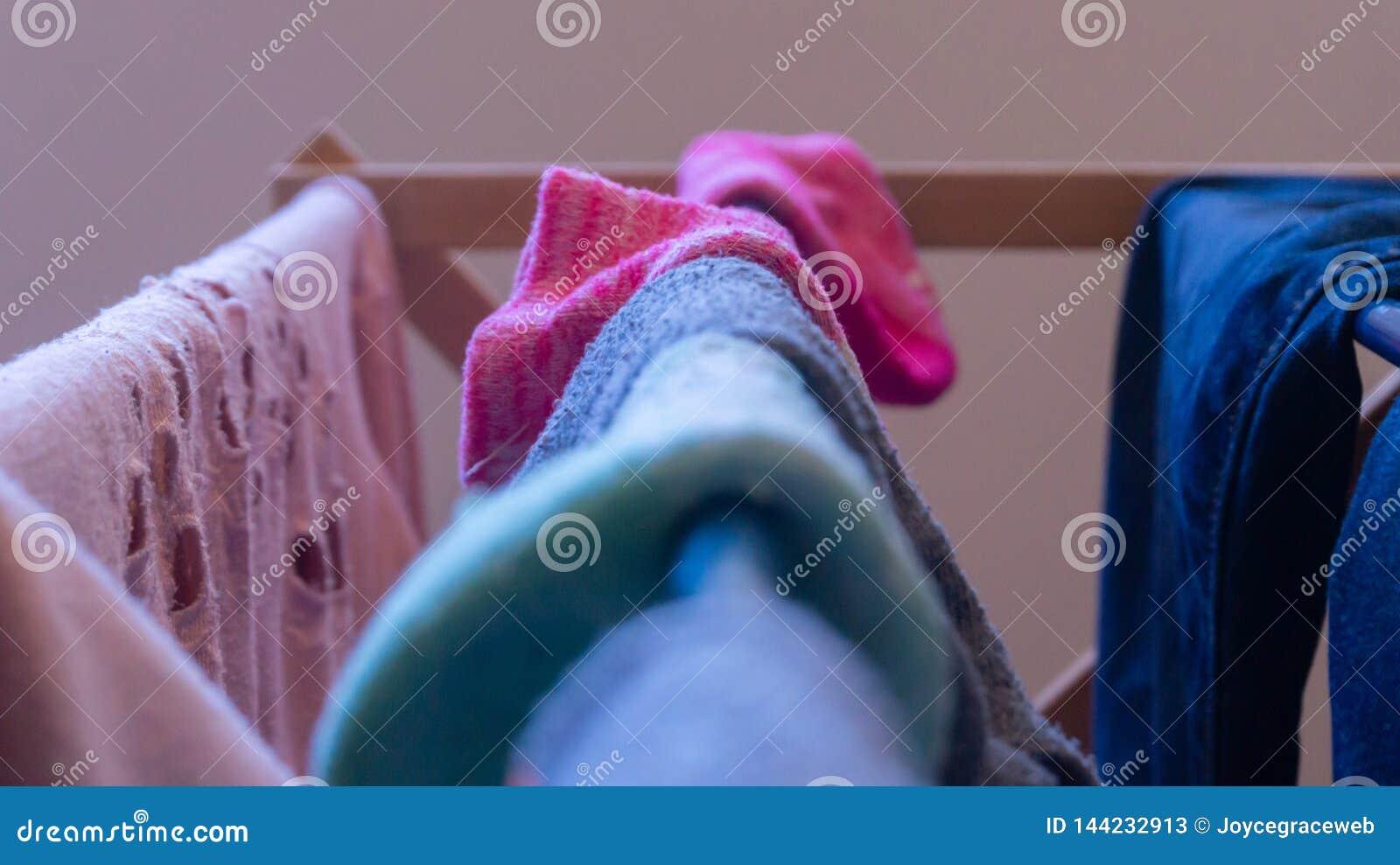 Fokus på en rosa socka som torkar på en tvätterikugge med annan kvinnas kläder och matchade dåligt sockor som göras suddig i förg