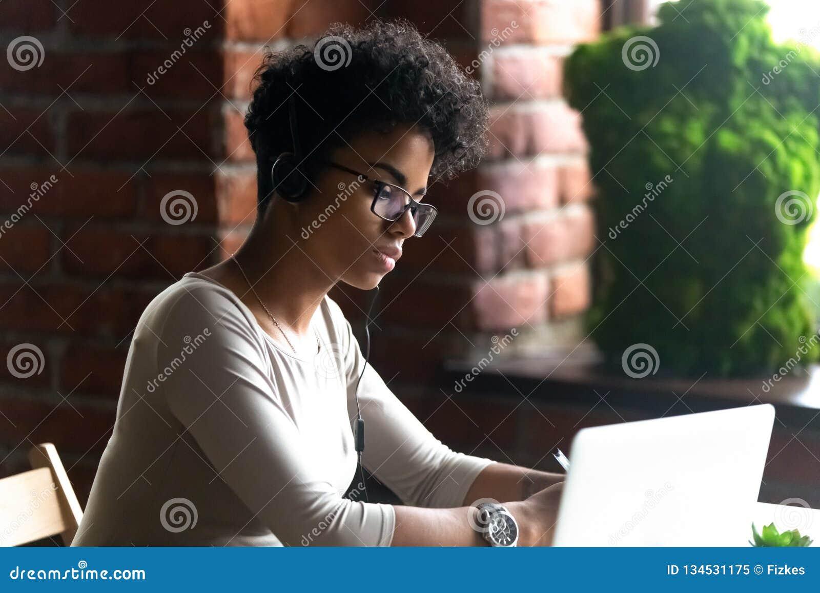 Fokuserad bärande hörlurar för afrikansk amerikankvinna genom att använda bärbara datorn
