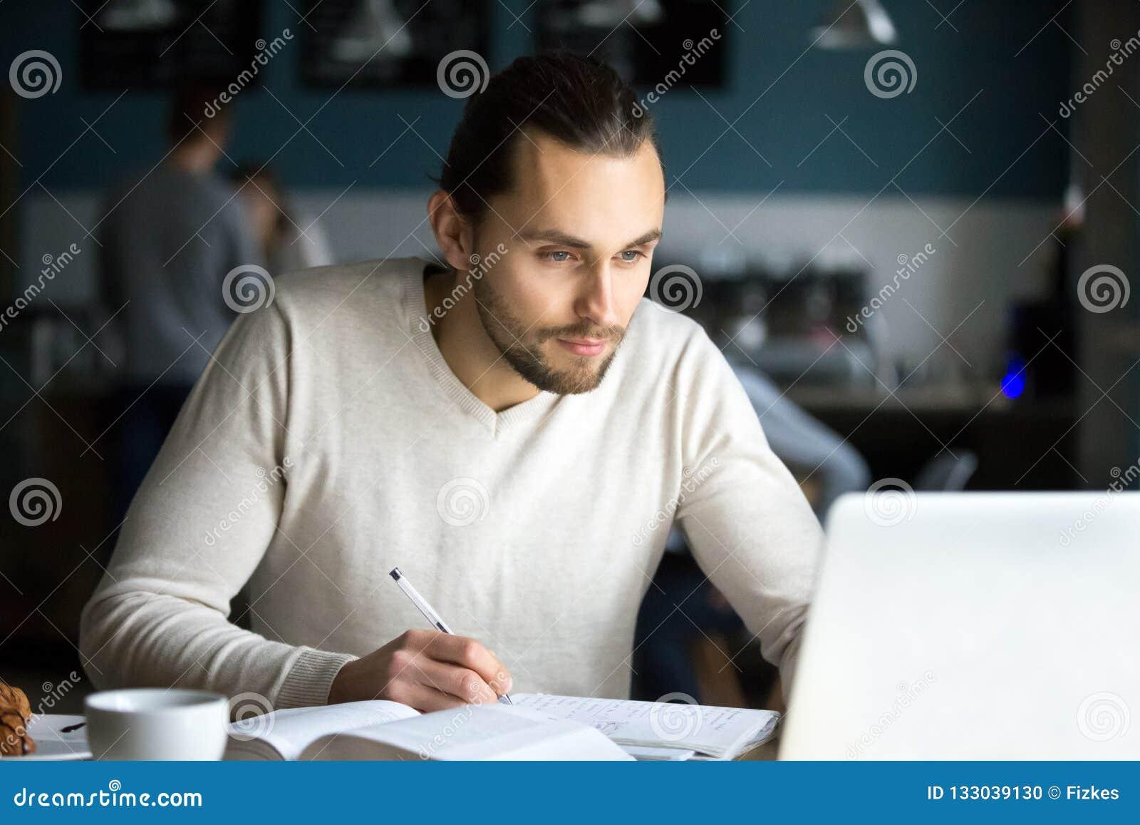 Fokuserad manlig student som studerar med bärbara datorn ut i kafé