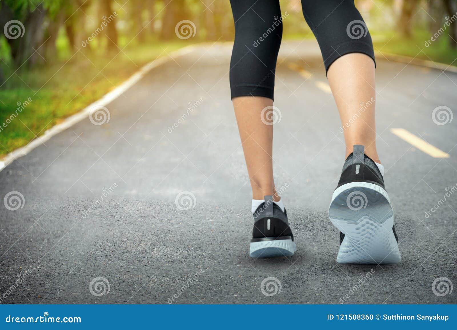 Folâtre le fond, pieds de coureur fonctionnant sur le plan rapproché de route sur la chaussure, la femme de sport courant sur la