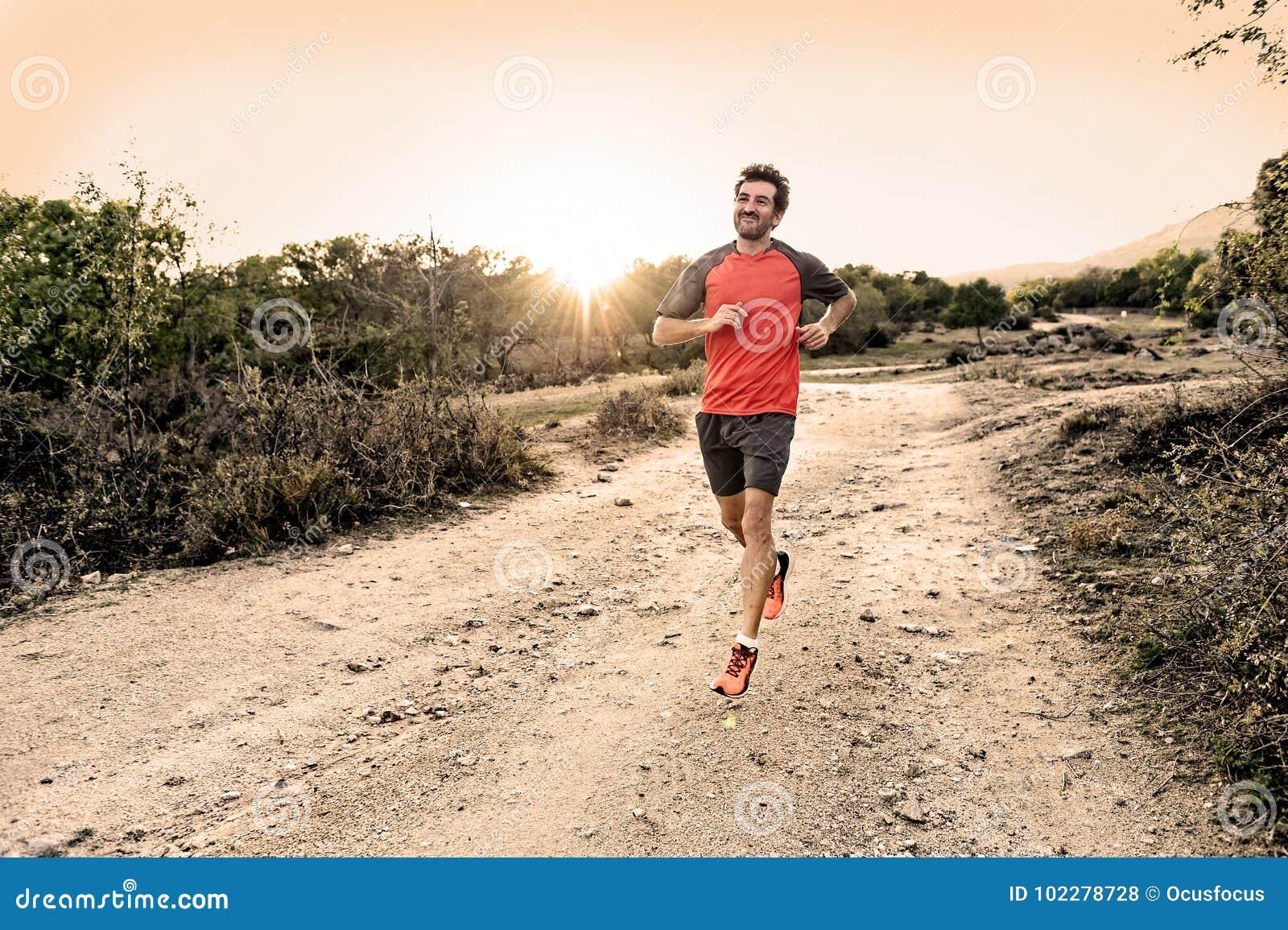 Folâtrez l homme avec les jambes sportives et musculaires déchirées fonctionnant en descendant outre de la route dans la séance d