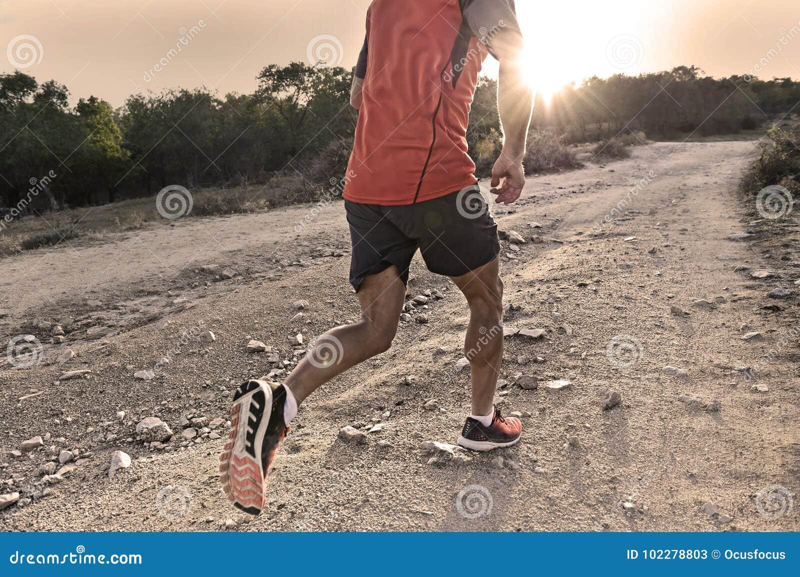 Folâtrez l homme avec les jambes sportives et musculaires déchirées fonctionnant vers le haut outre de la route dans la séance d