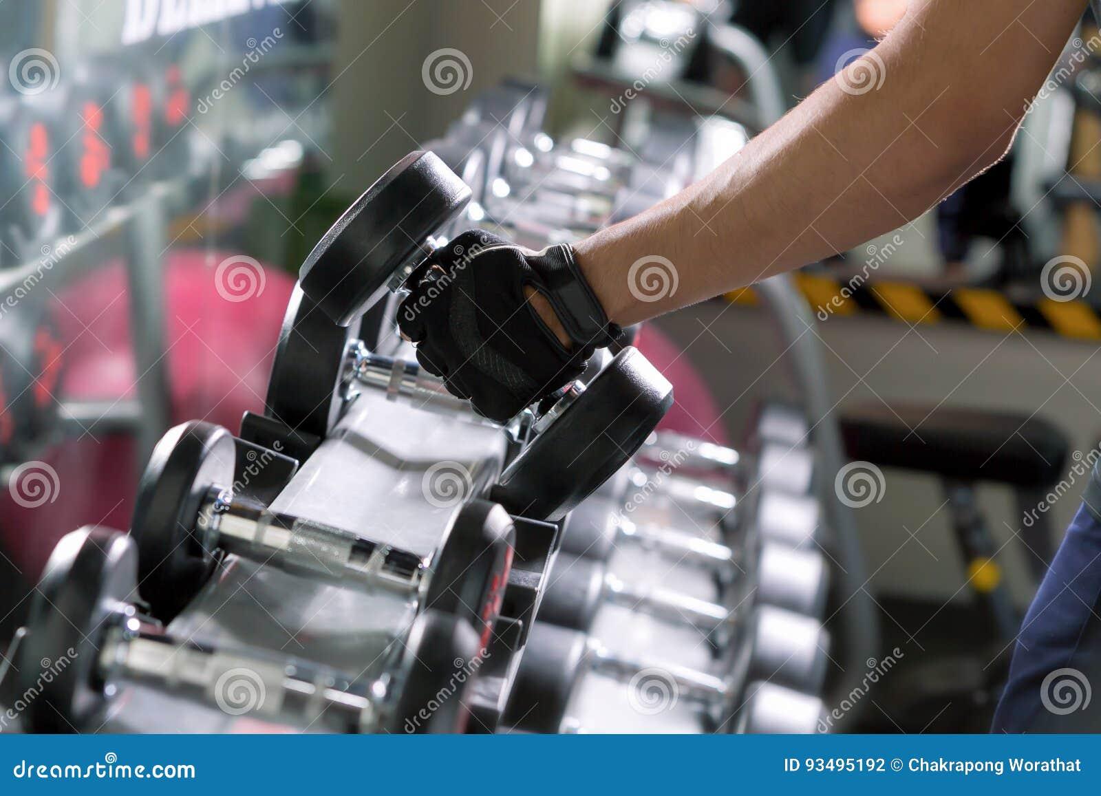Folâtrez l homme faisant des rangées d haltère d un-bras de métal dans le gymnase moderne