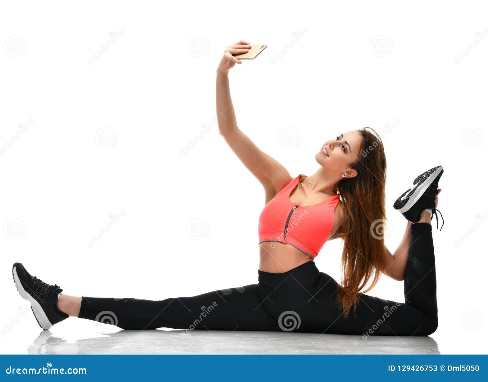 Folâtrez la gymnastique de femme faisant en étirant la séance d entraînement d exercice de forme physique et faites le selfie sur