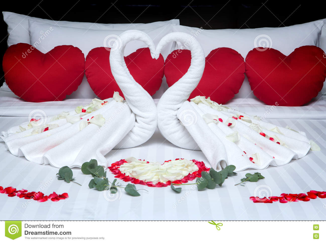 Fold a towel swan for decorations with rose petals on bed for Bed decoration with rose petals