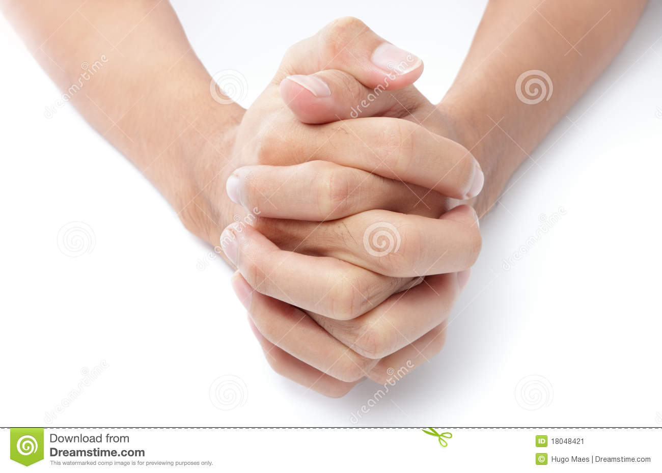 ... two hands folded with intertwined fingers praying on a white desktop