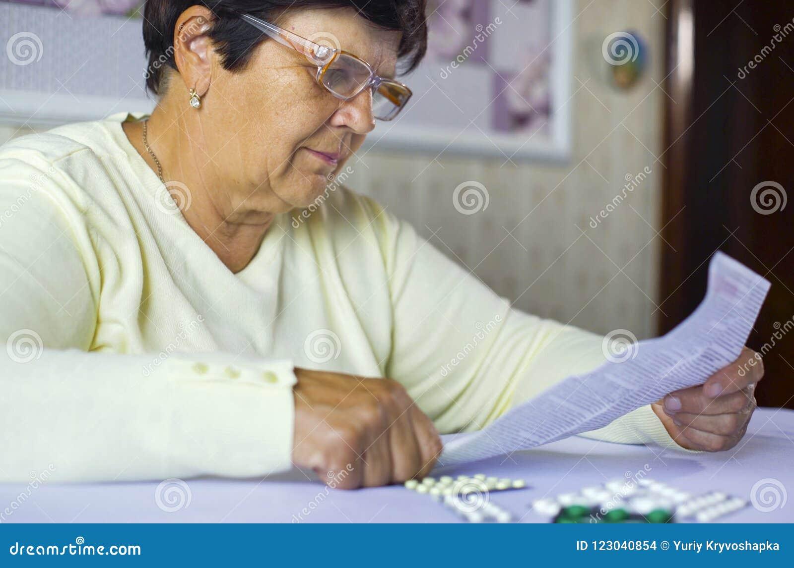 Folha de informação superior da leitura da mulher da medicina prescrita que senta-se na tabela em casa